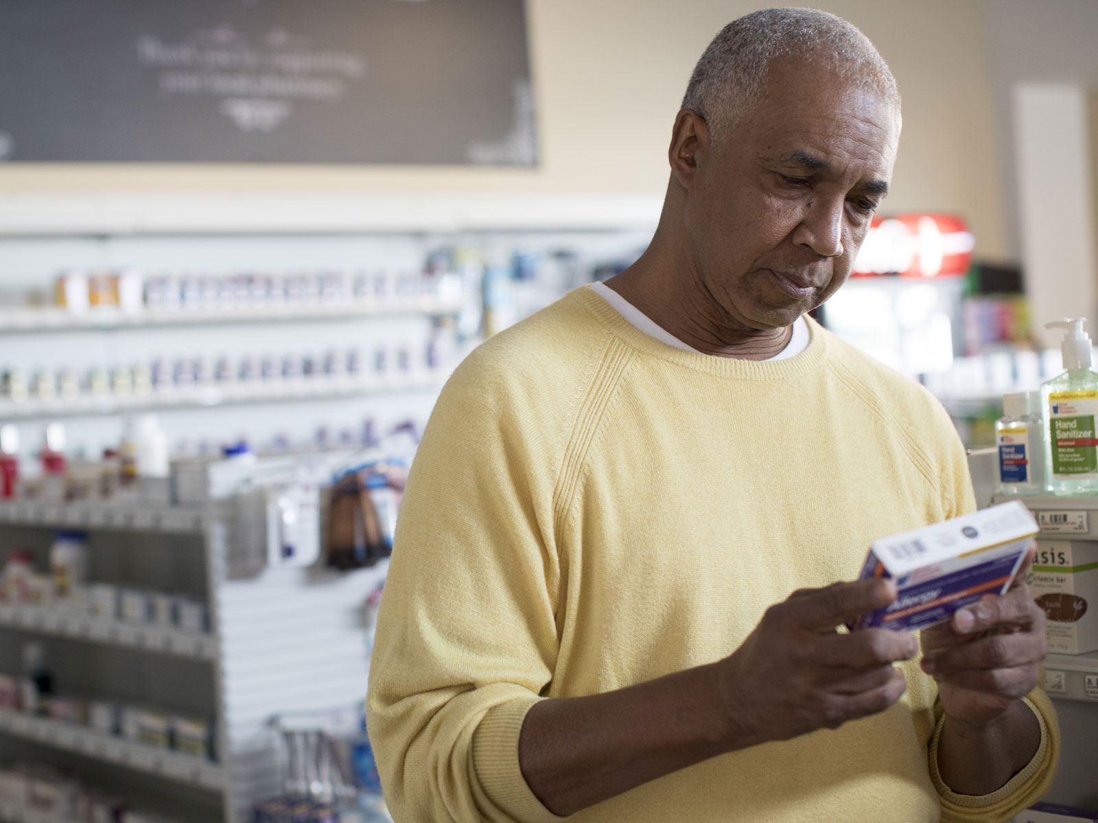 A man in the pharmacy aisle looking over the instructions on the back of an over the counter prescription.