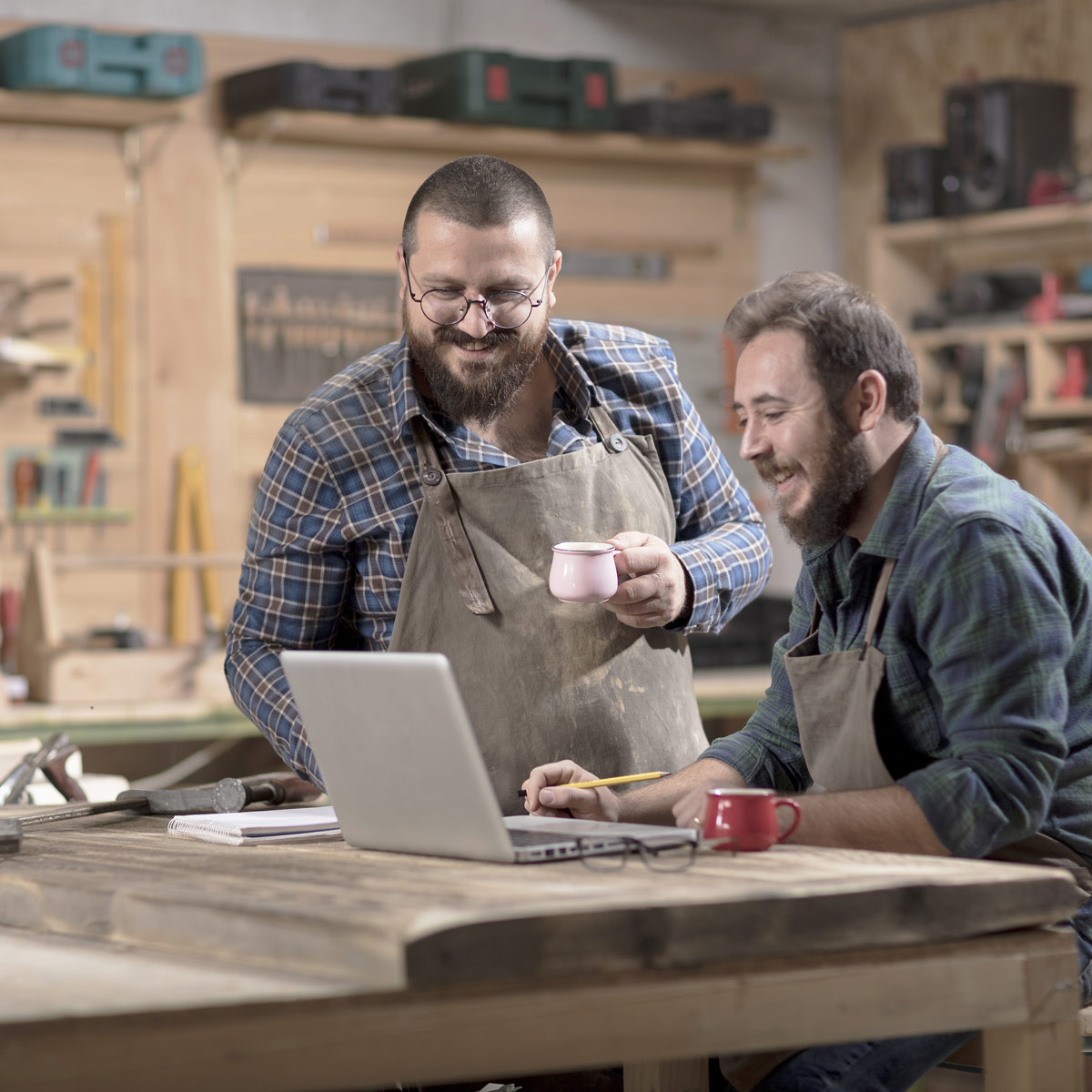 Two employees working on a laptop inside a woodworking design shop