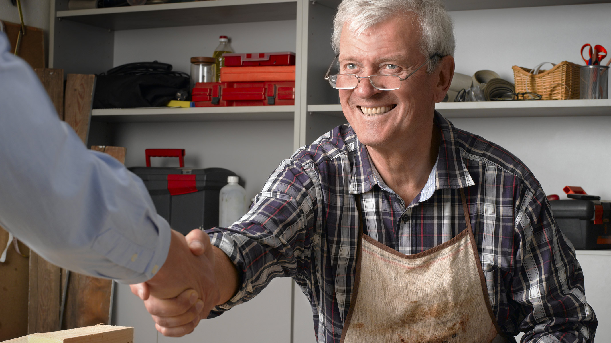 Business owner shaking customer's hand inside his repair shop