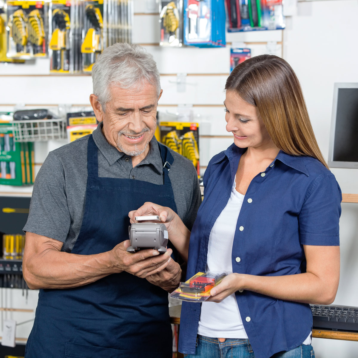 Hardware shop owner reviewing sales receipt with a customer inside store