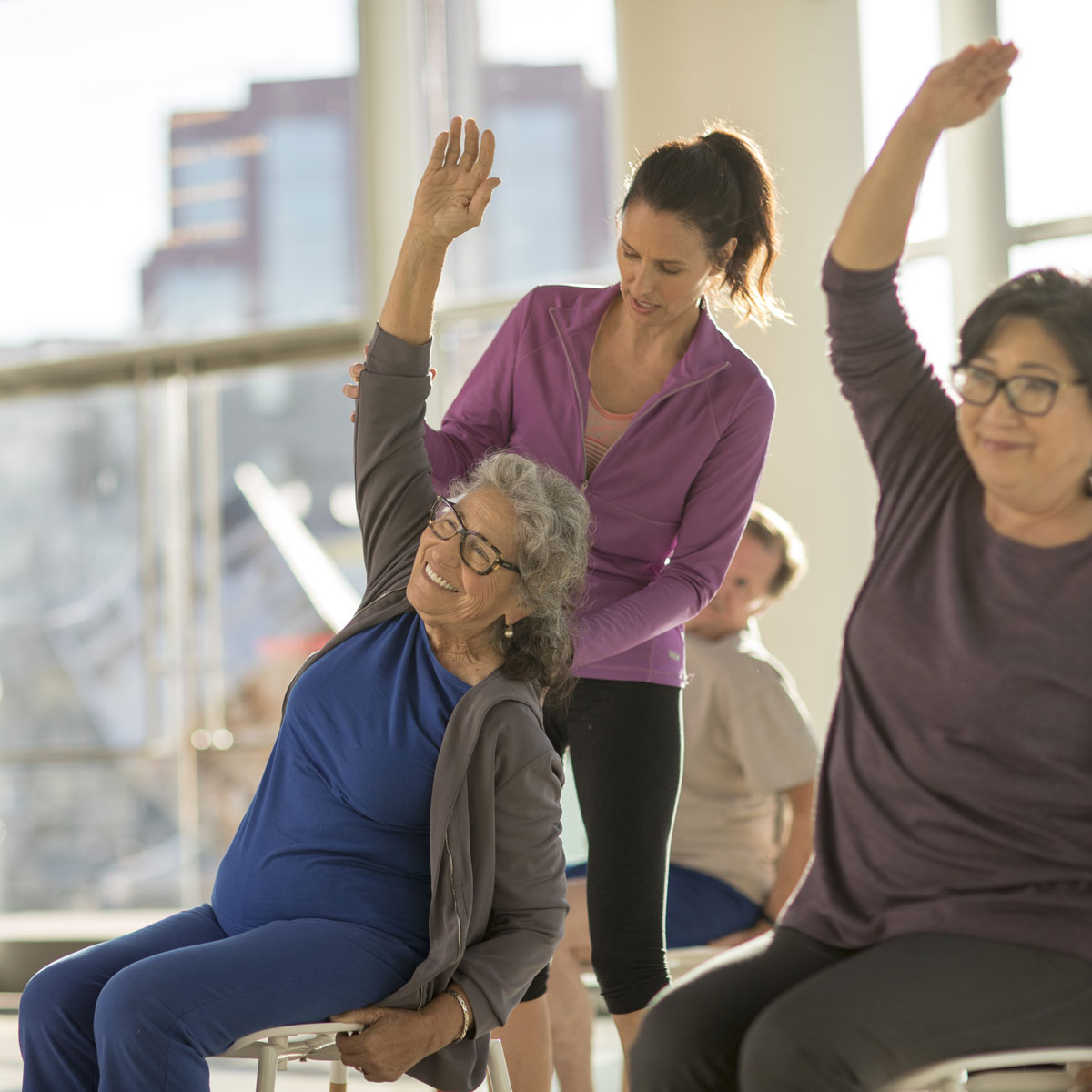 A group of people in exercise clothes sitting in chairs, stretching their right arm over their heads while a trainer supports one woman's stretch.