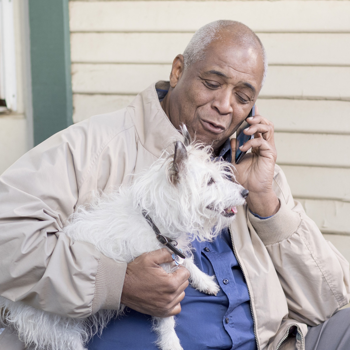 Man on a mobile phone holding a dog