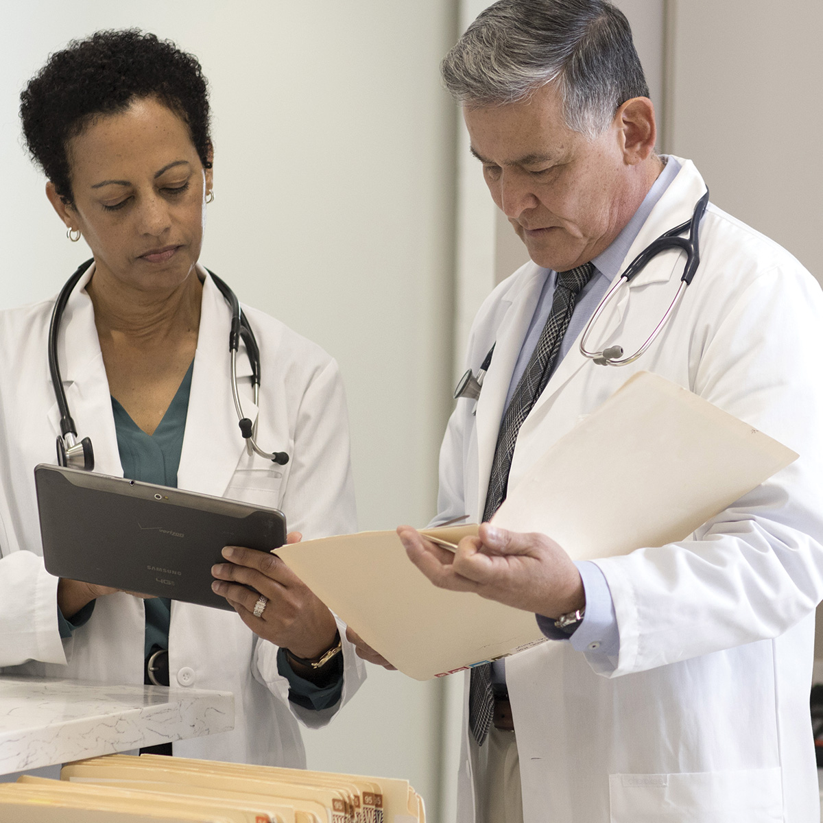 Two doctors with focused expressions look at a tablet.