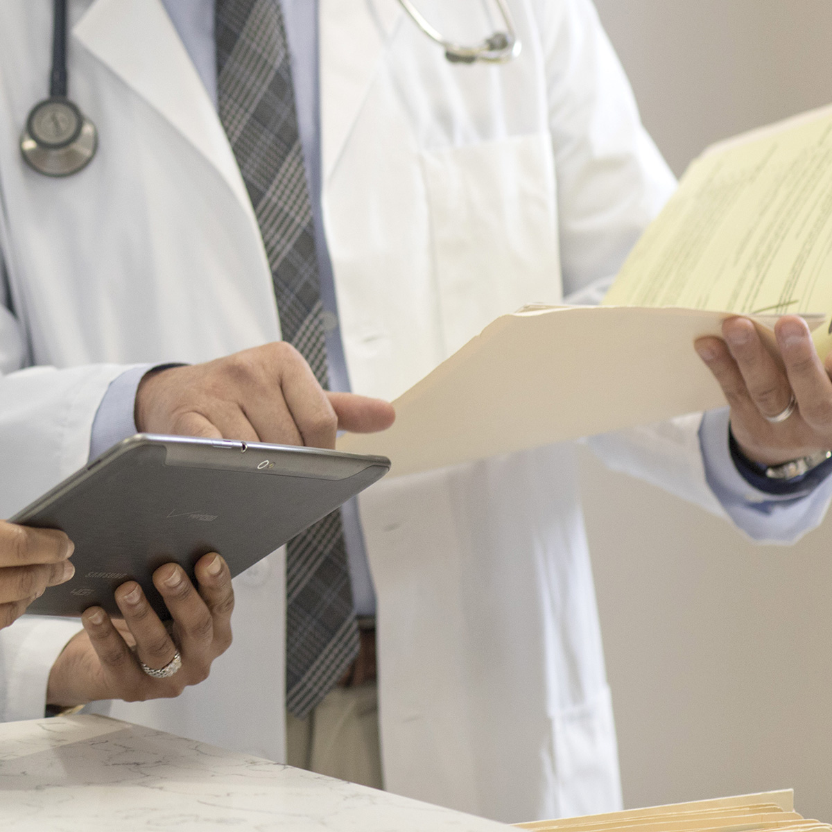 A close up on two doctors hands as one reviews information on a tablet and the other references a file.