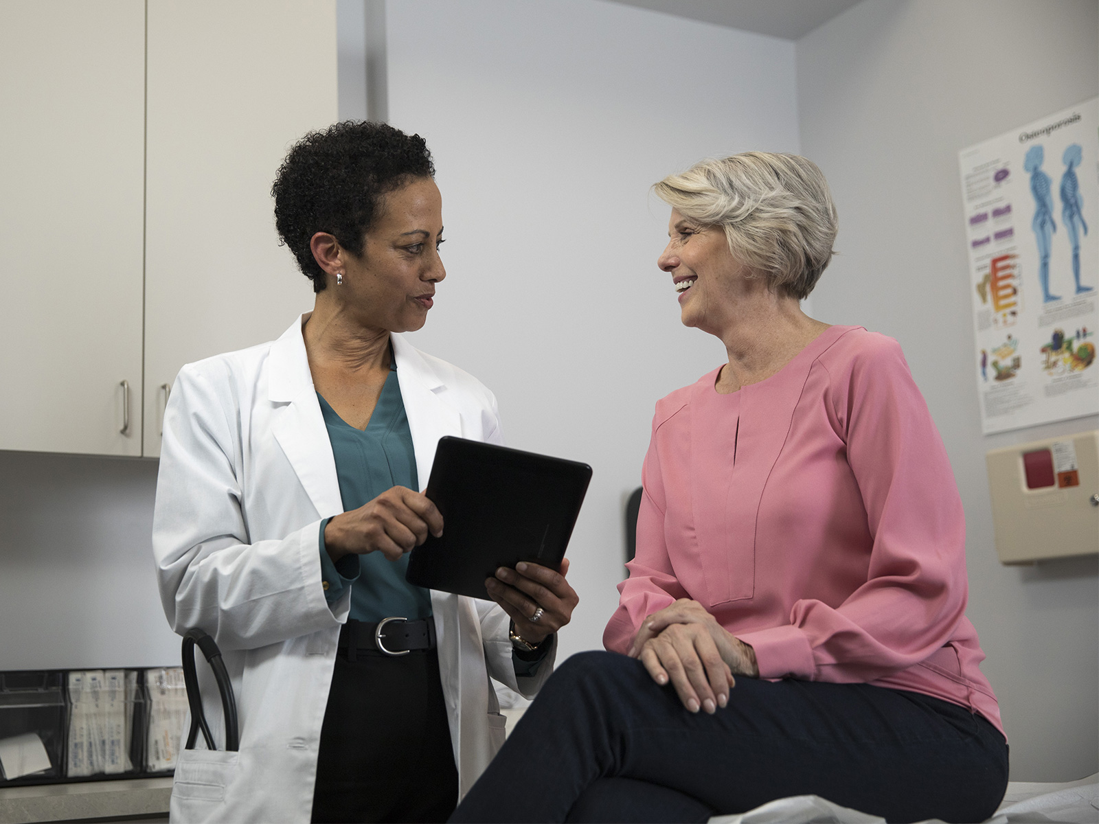 A patient smiles while a doctor shows her something on a screen.