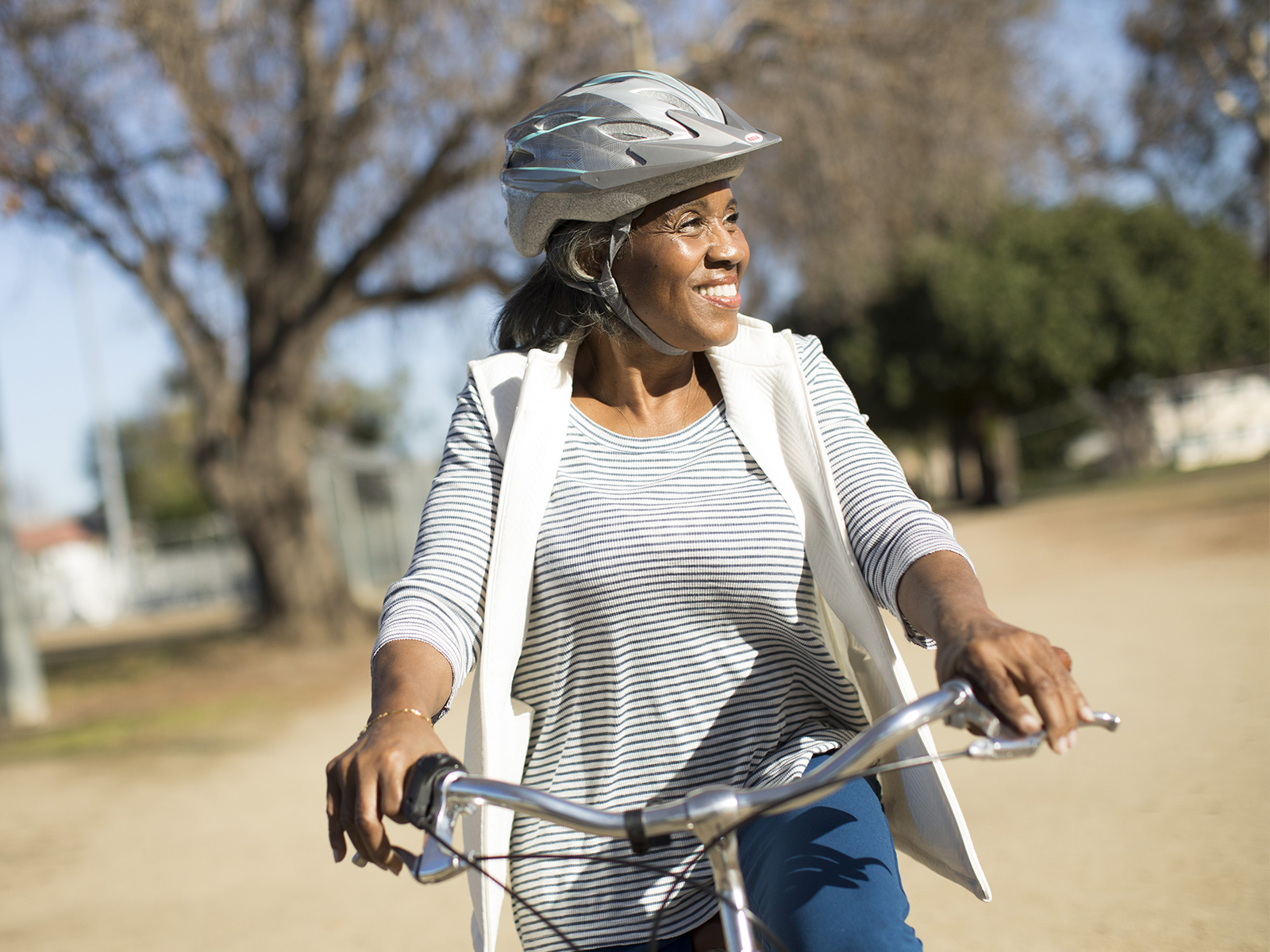 A woman smiles while riding her bike outside