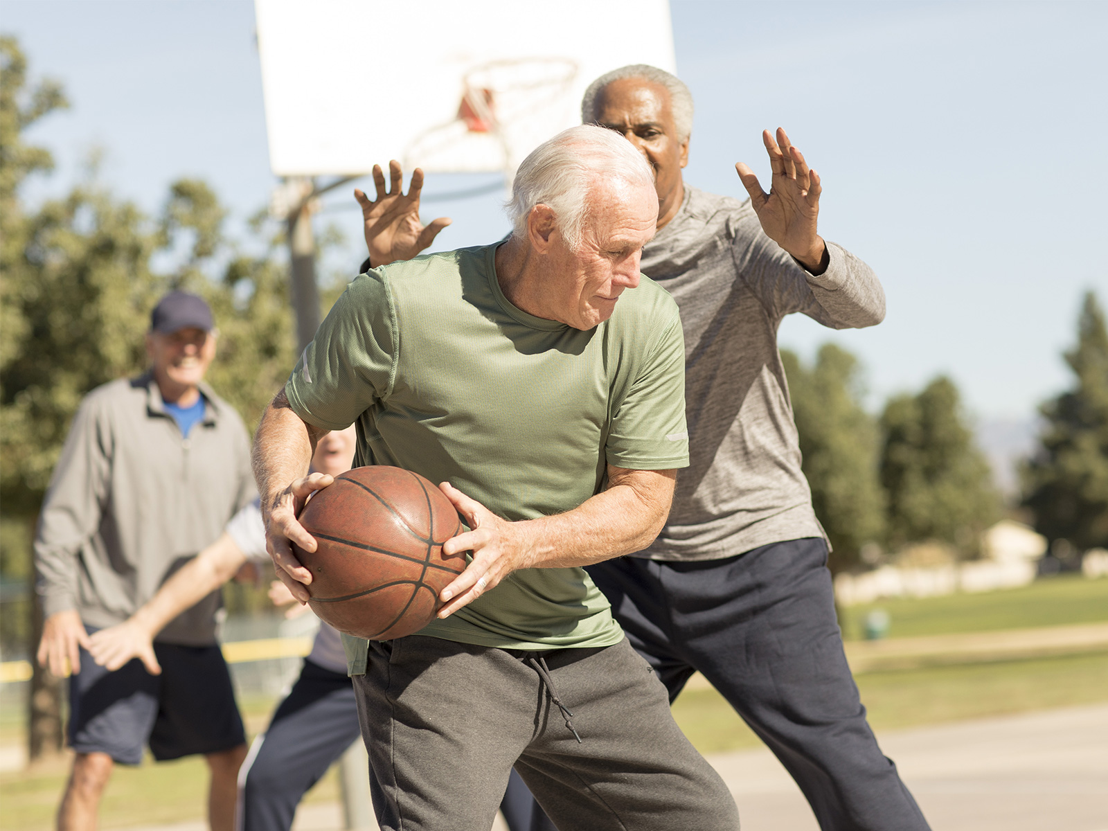 a group of men play a pickup game of basketball in the park