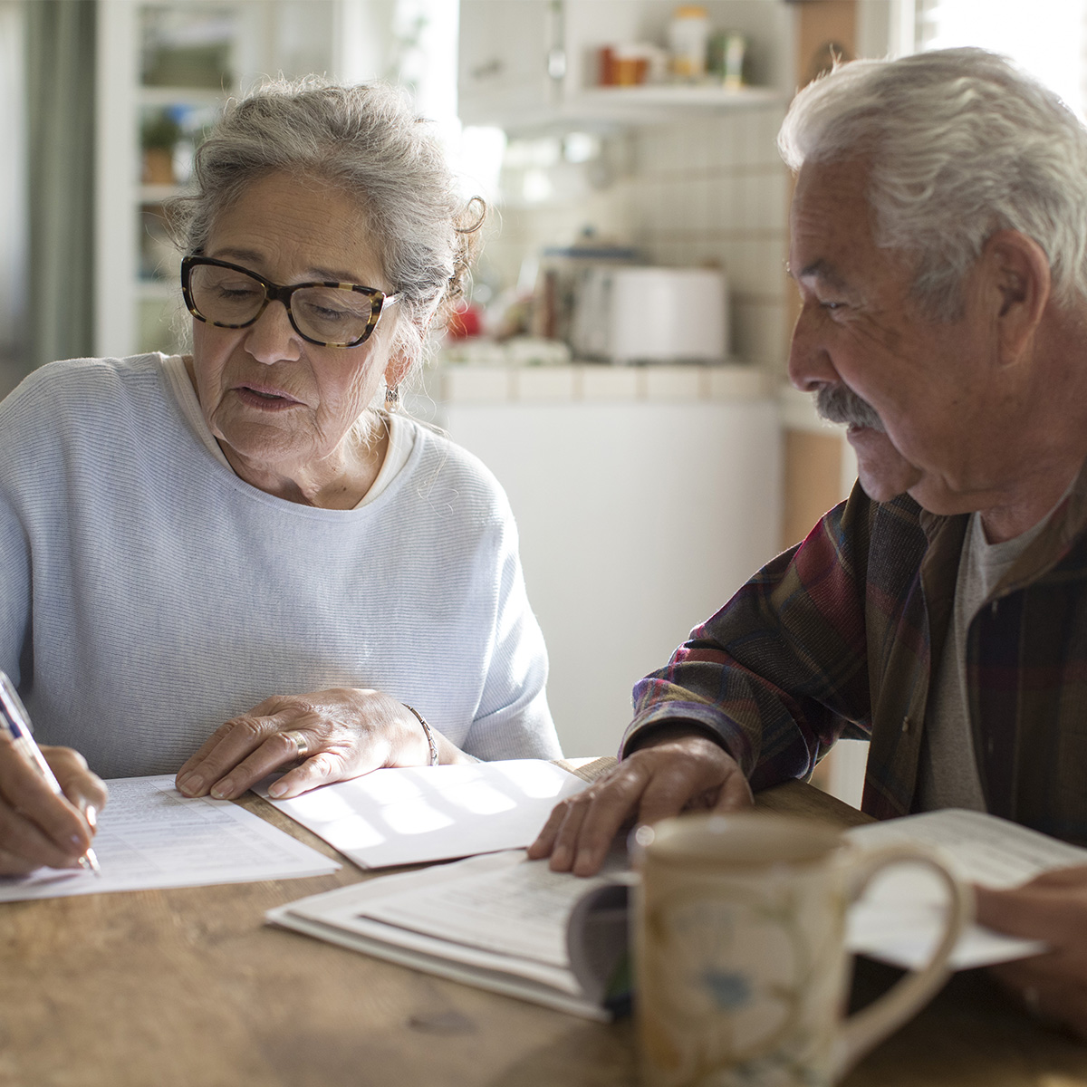 A caregiver helps a senior fill out paperwork