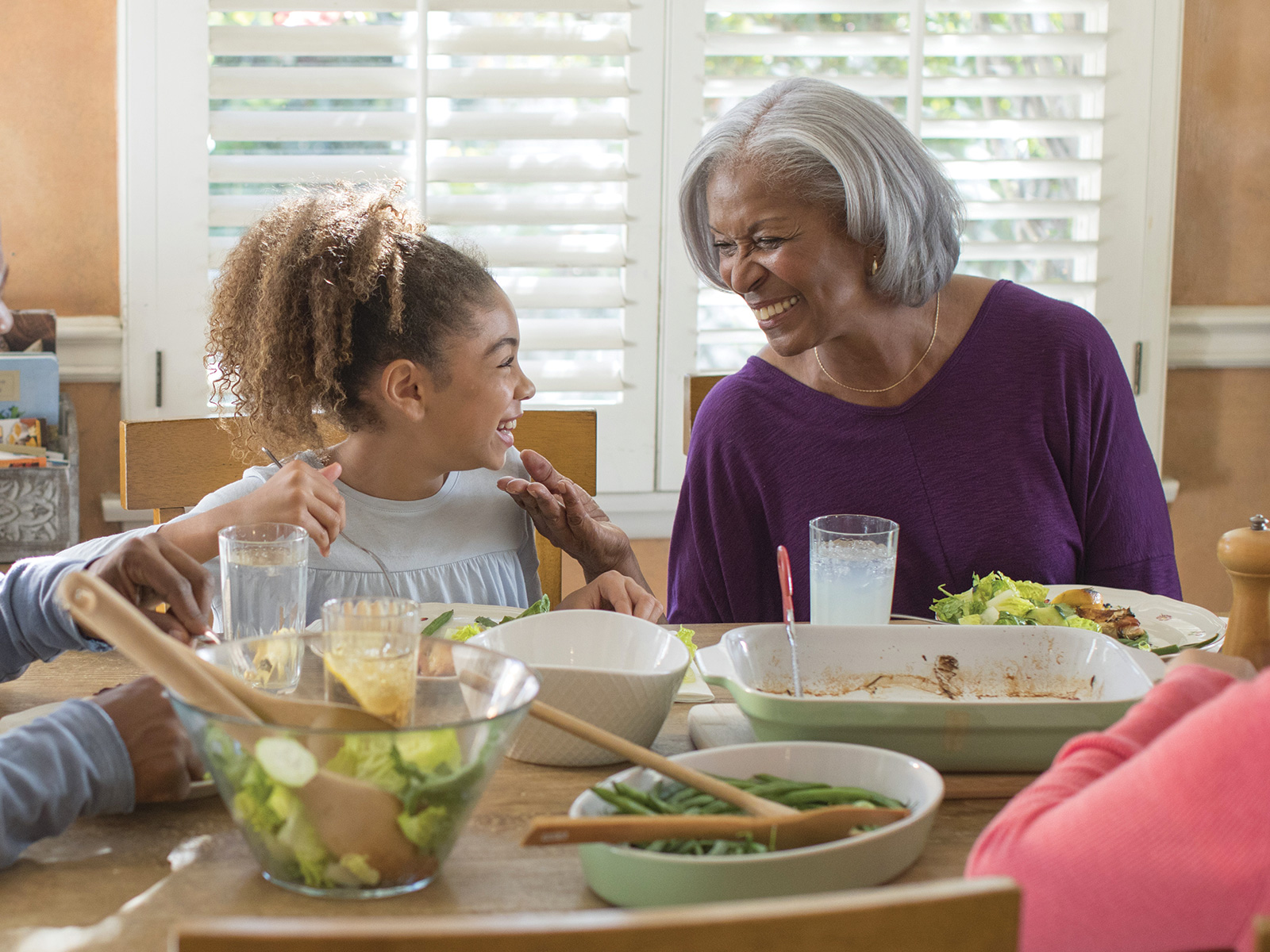 A grandmother and granddaughter smile at the dinner table.