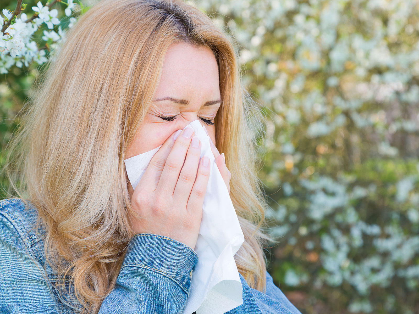 A woman standing outside sneezes into a tissue