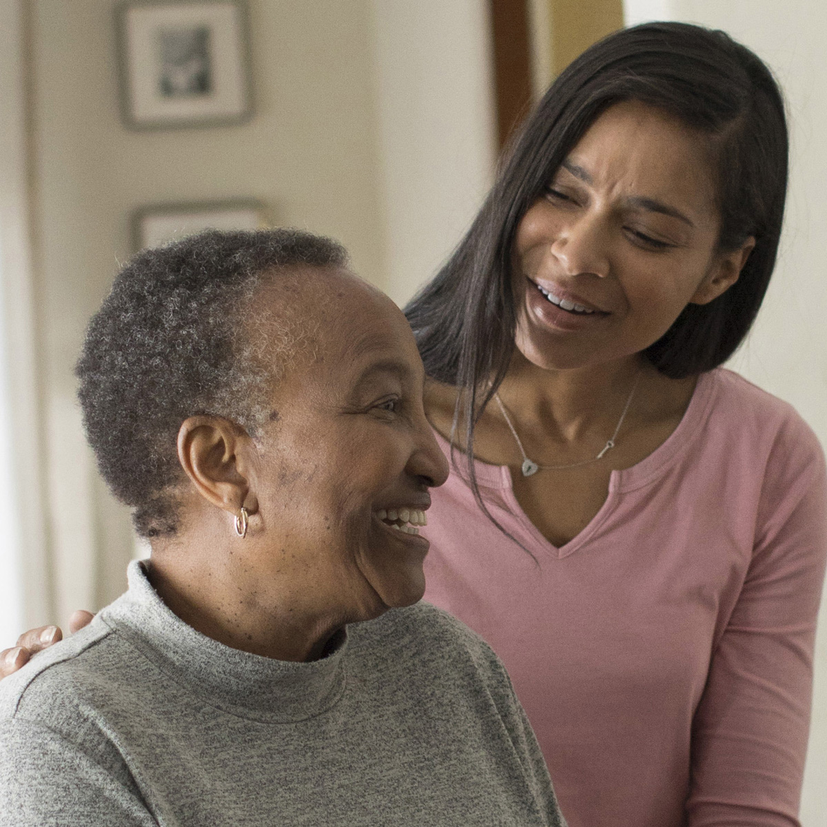 A caregiver and her loved one laugh together