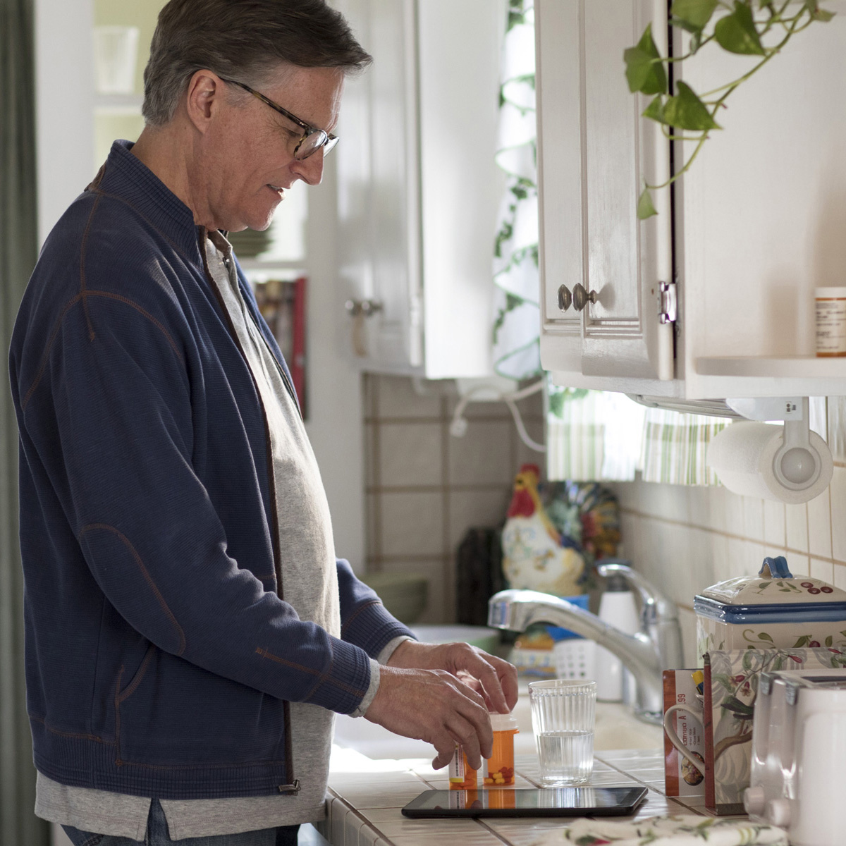 A man stands in front of a kitchen sink while getting ready to take his medicine.