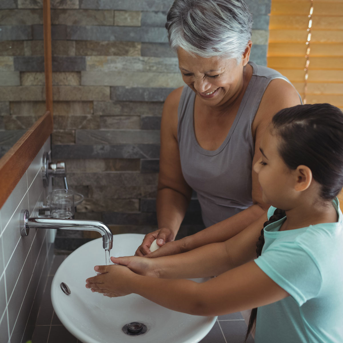 A grandmother helps her granddaughter wash her hands.