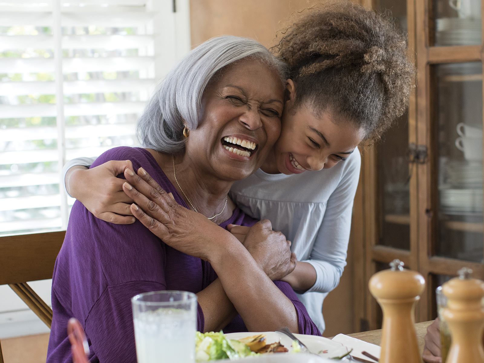 A young girl hugs her grandma while both are laughing at the dinner table.