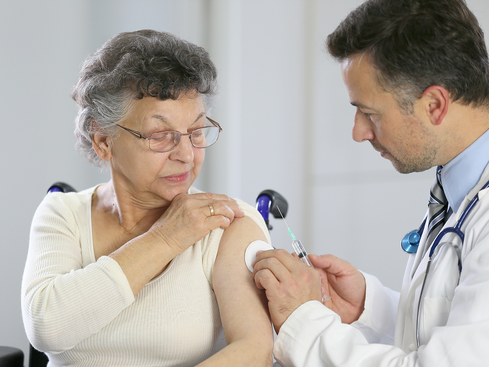 A doctor administers a shot to a patient.