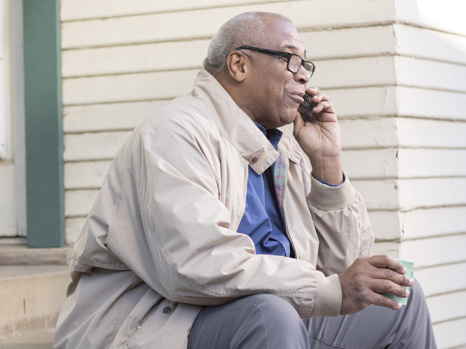 Senior man sitting on porch steps with mobile phone