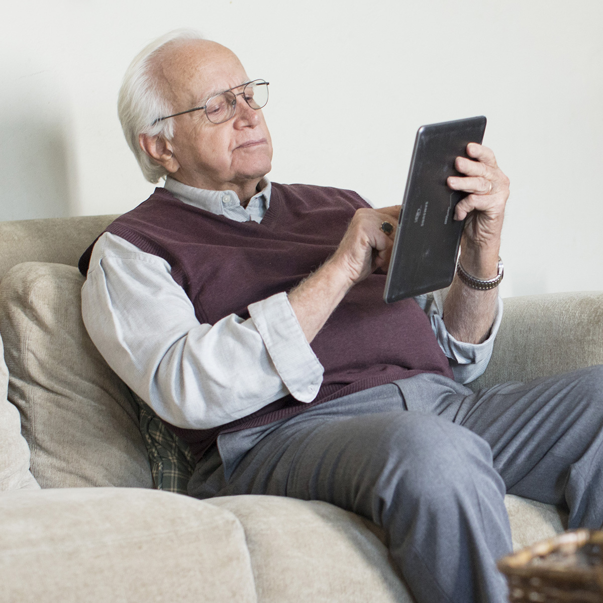 A man sits on a couch and uses a tablet.