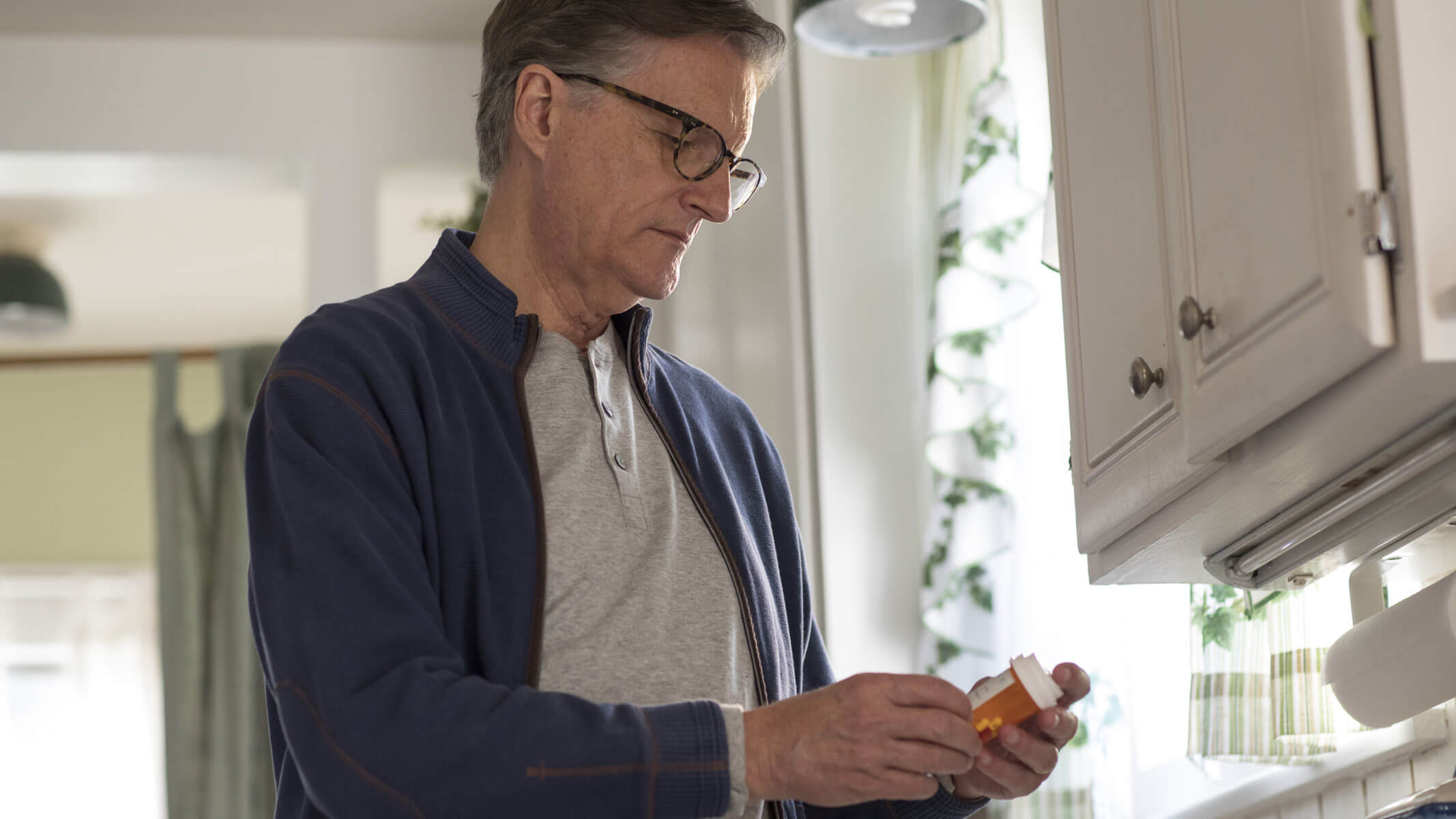 Man reads medication label in kitchen.
