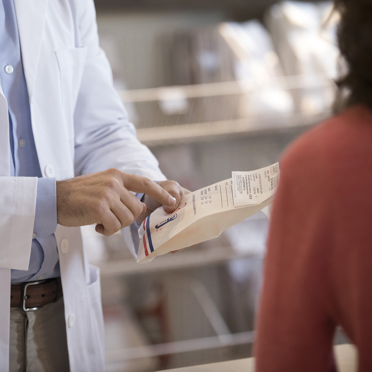A close up on a pharmacist holding a prescription pointing at the directions.