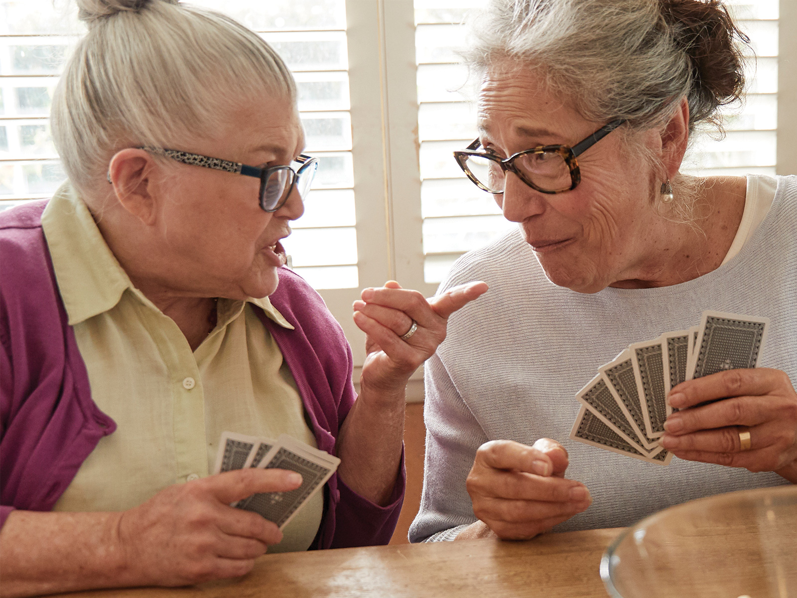 Two women sitting at table talking and playing cards
