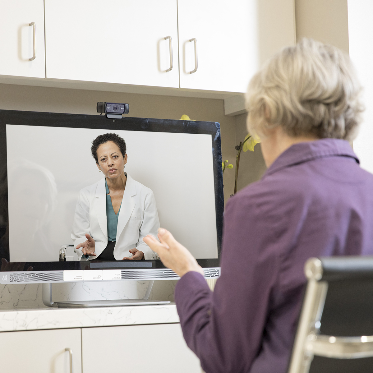 Woman using video chat to confer with doctor