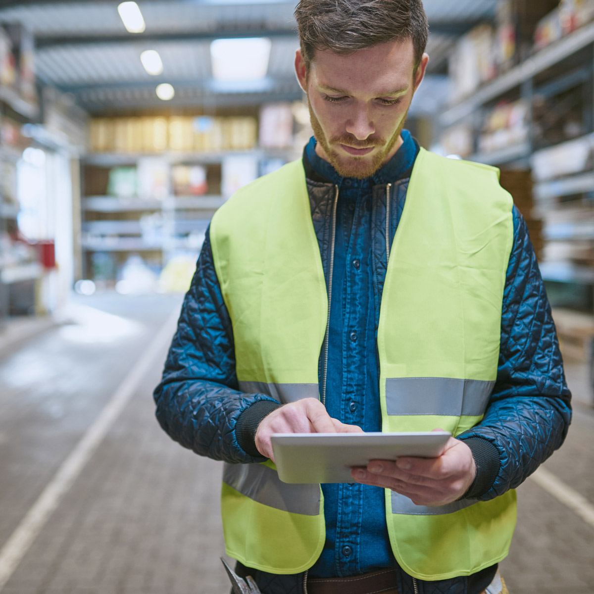 Man in high visibility vest looking at tablet screen in a warehouse