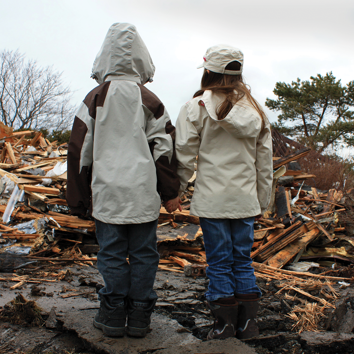 Two children standing in front of destroyed house.