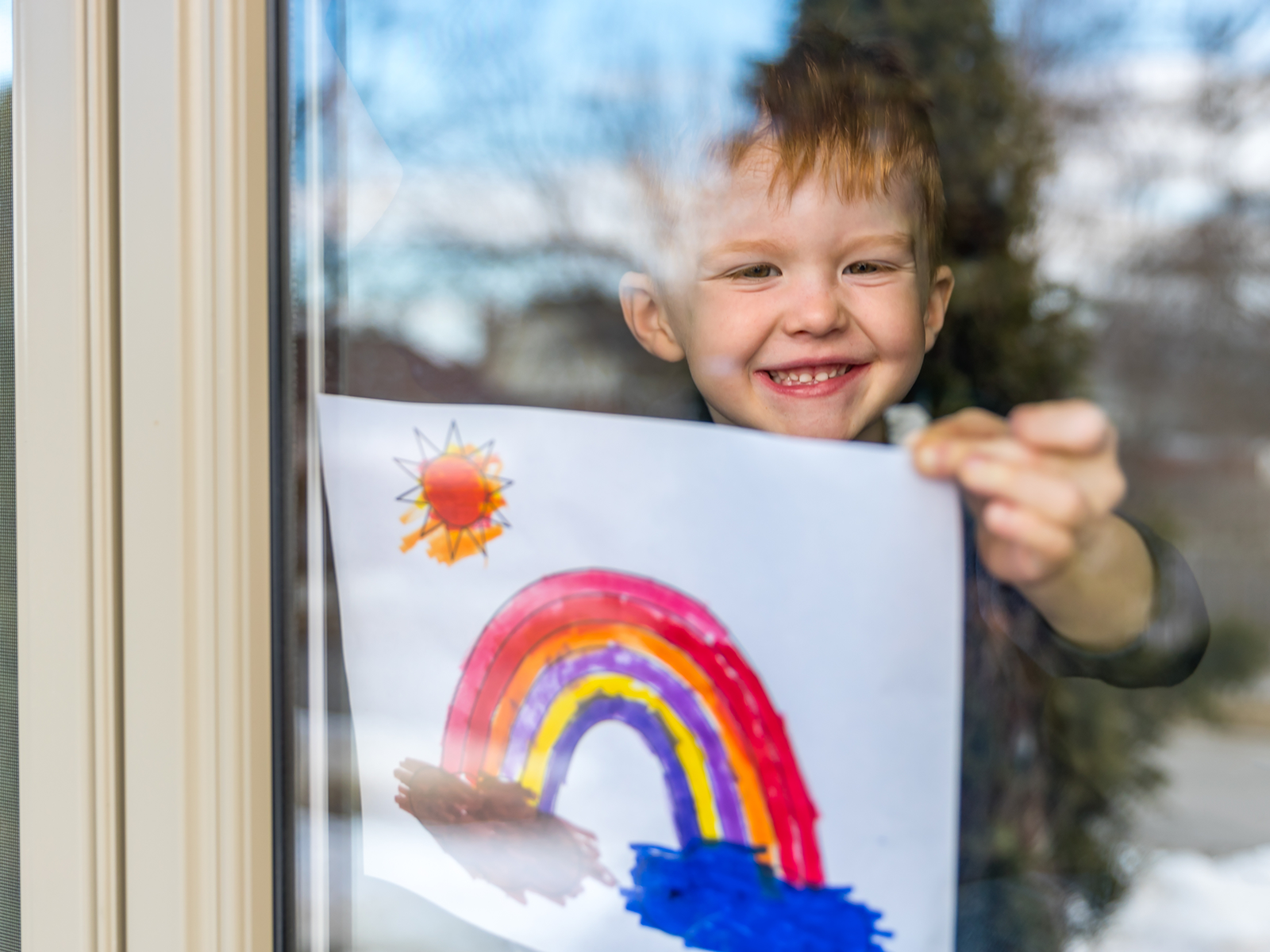 little boy at home behind a window holding up a rainbow drawing