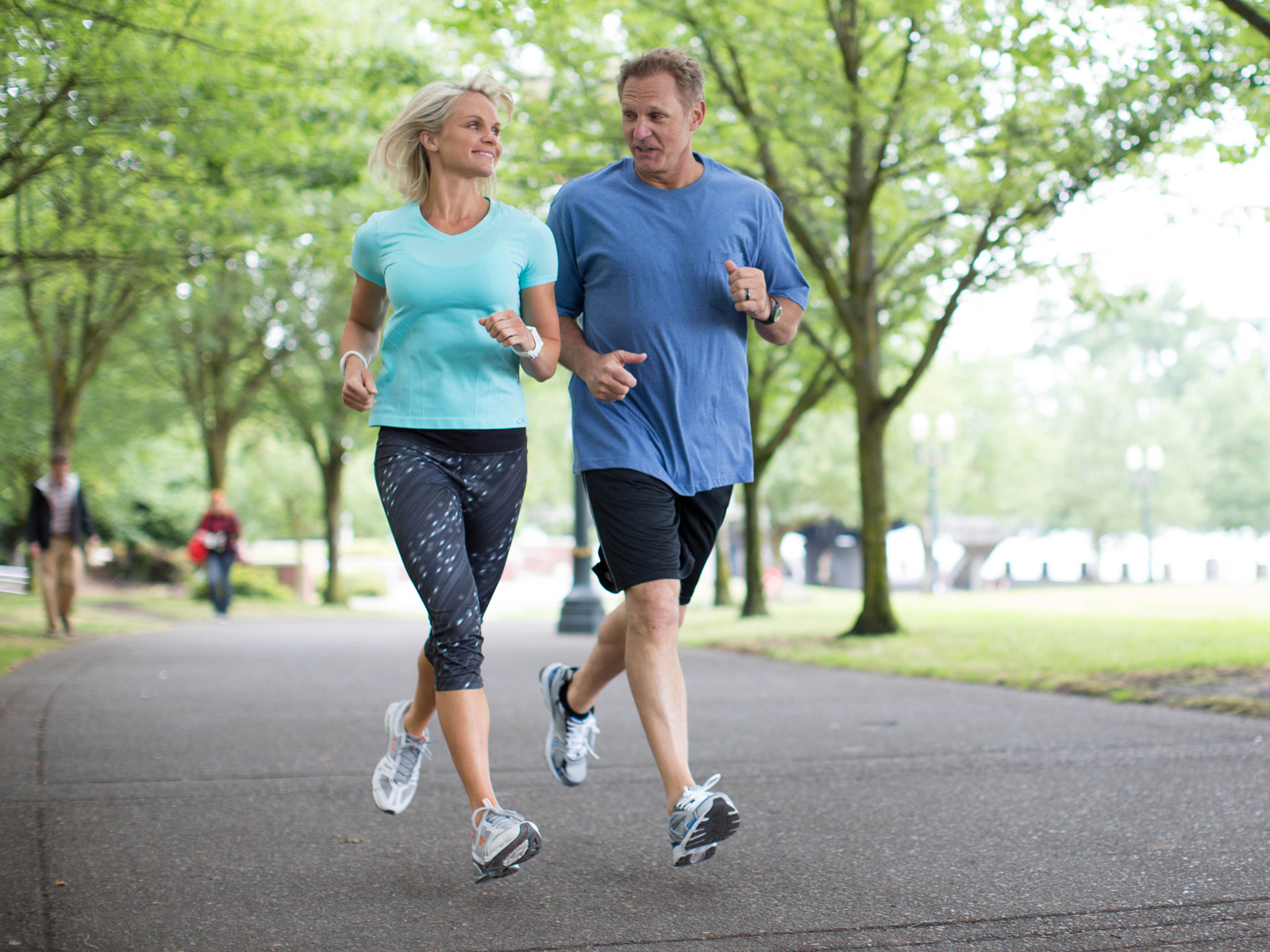 a man and woman enjoy jogging in the park while they wear activity trackers