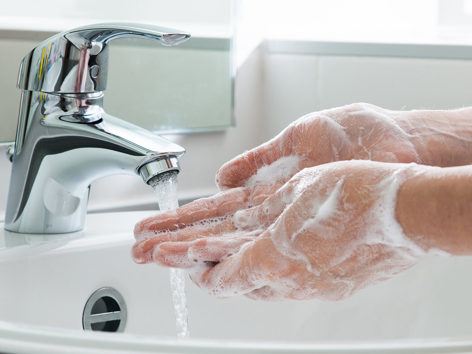 Person vigorously washing hands in sink