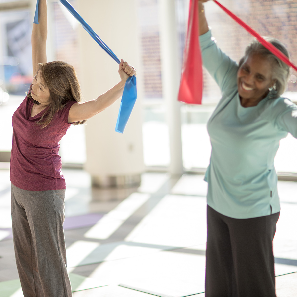 Participants in an exercise class bend to the side while stretching an elastic band over their heads.