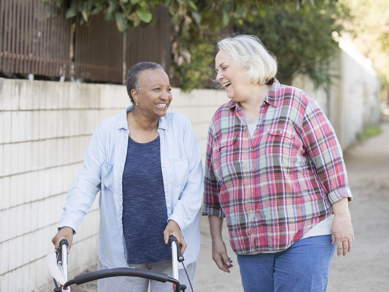 An older woman assisted by a walker enjoys a stroll outside with her caregiver.