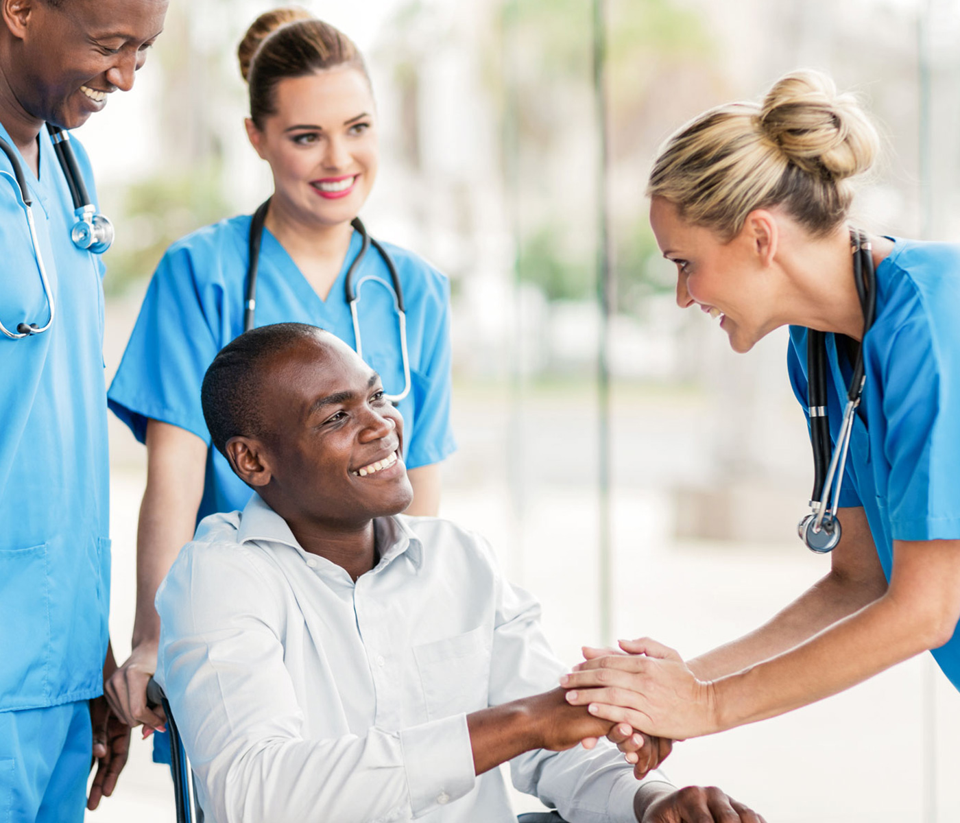 Man in wheelchair smiling and holding the hand of a healthcare worker in front of him and two smiling healthcare professionals behind him.
