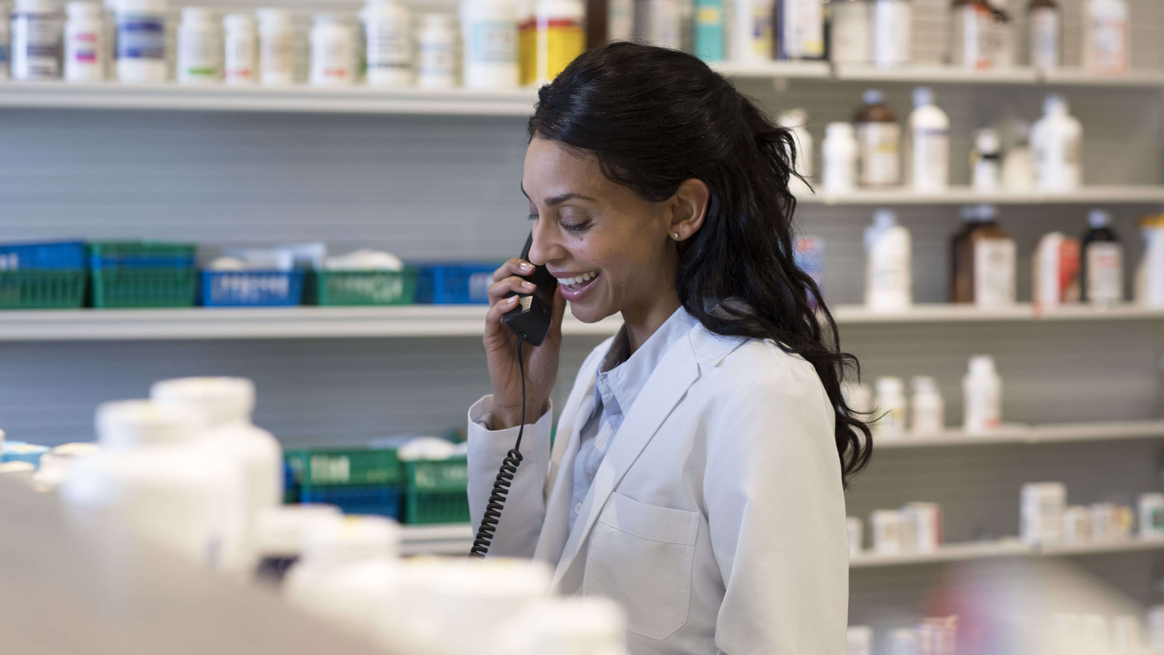 Smiling woman pharmacist talking on the phone.