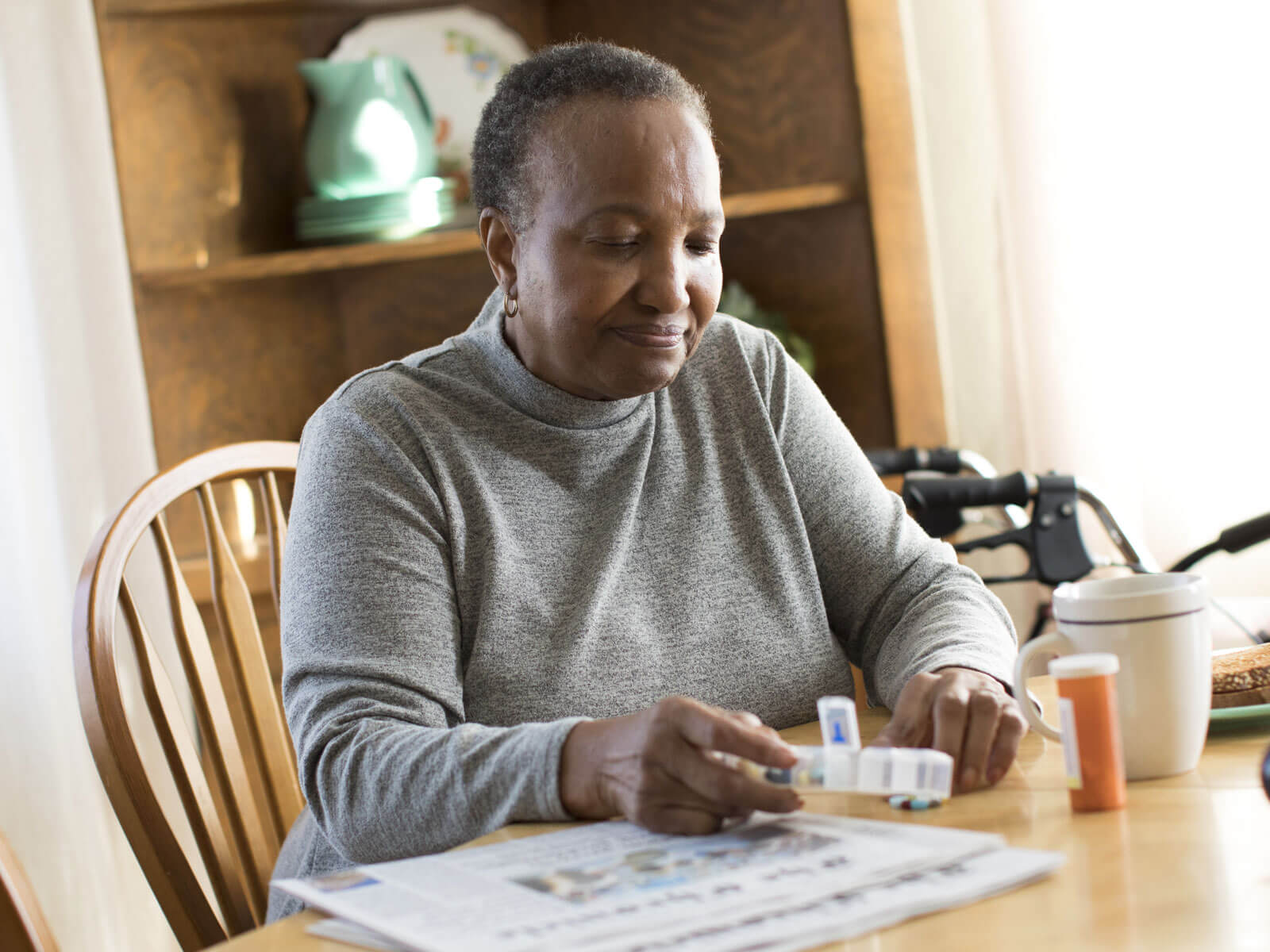 A woman sits at a kitchen table organizing prescriptions into a weekly pill box.