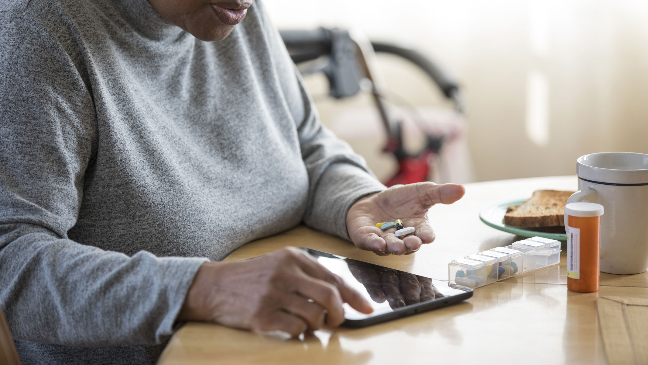 Woman looks up information on her tablet at the kitchen table while holding medication in the other hand.