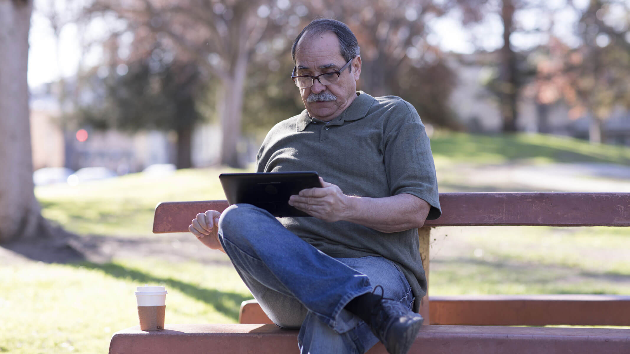 An older man sits on a park bench reading from a tablet.