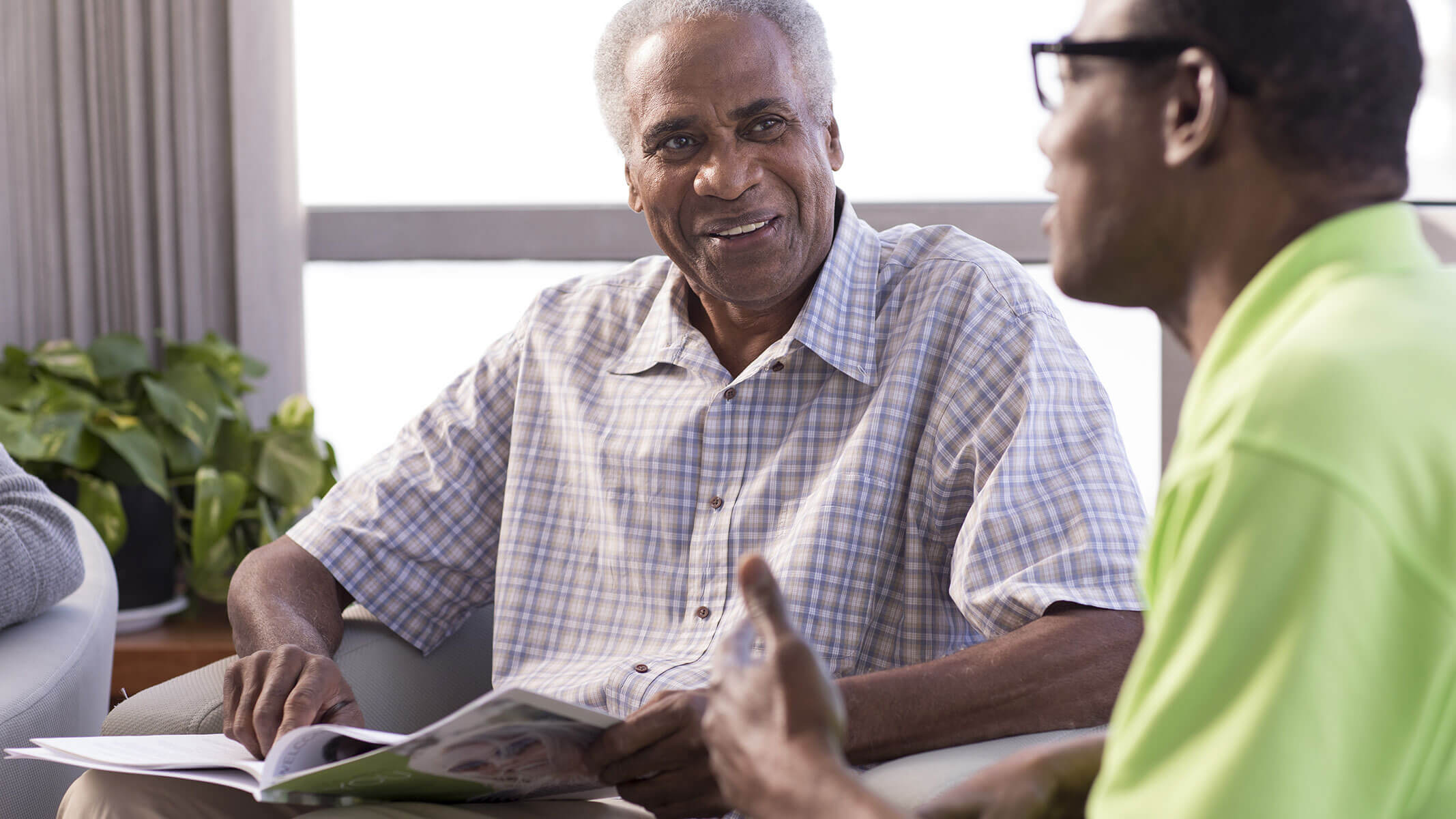 An elderly man flips through a Humana brochure while talking to a Humana agent.