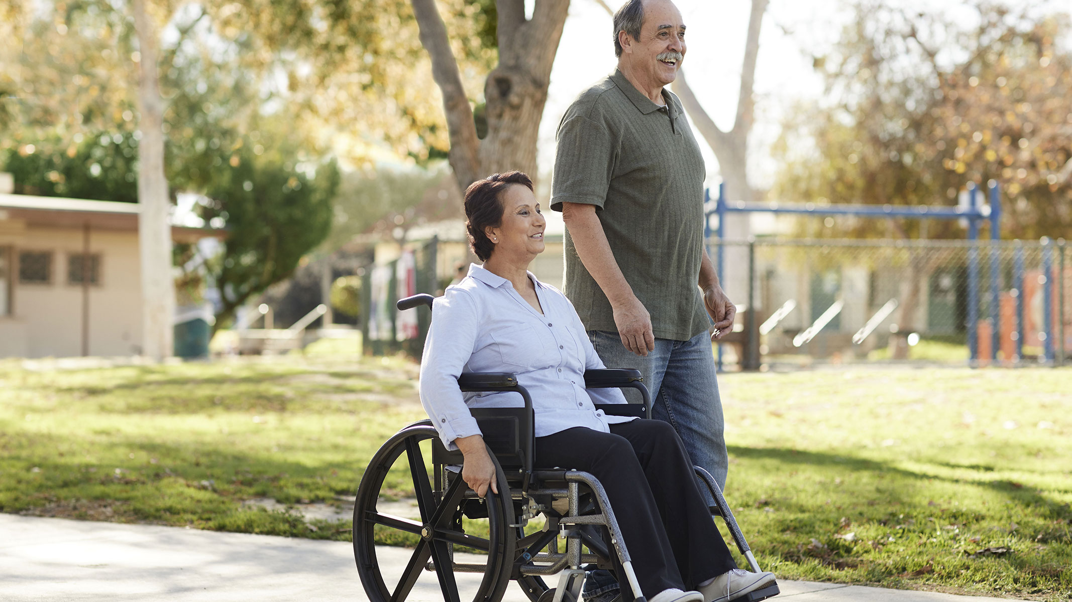 A man and woman in a wheel chair go for a stroll by a park.