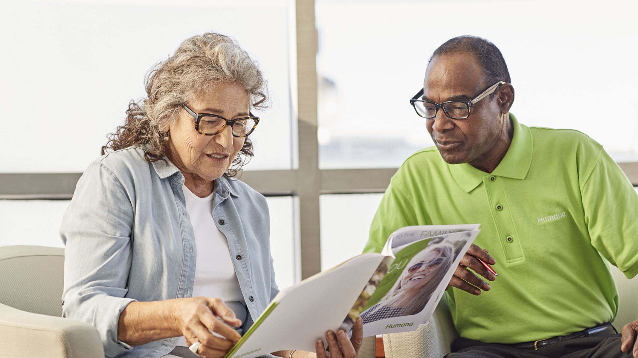 Two senior citizens read through a brochure on Humana insurance plans.