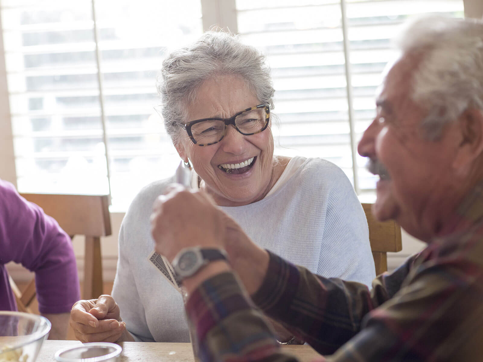 A senior couple laughs together while sitting at a kitchen table.