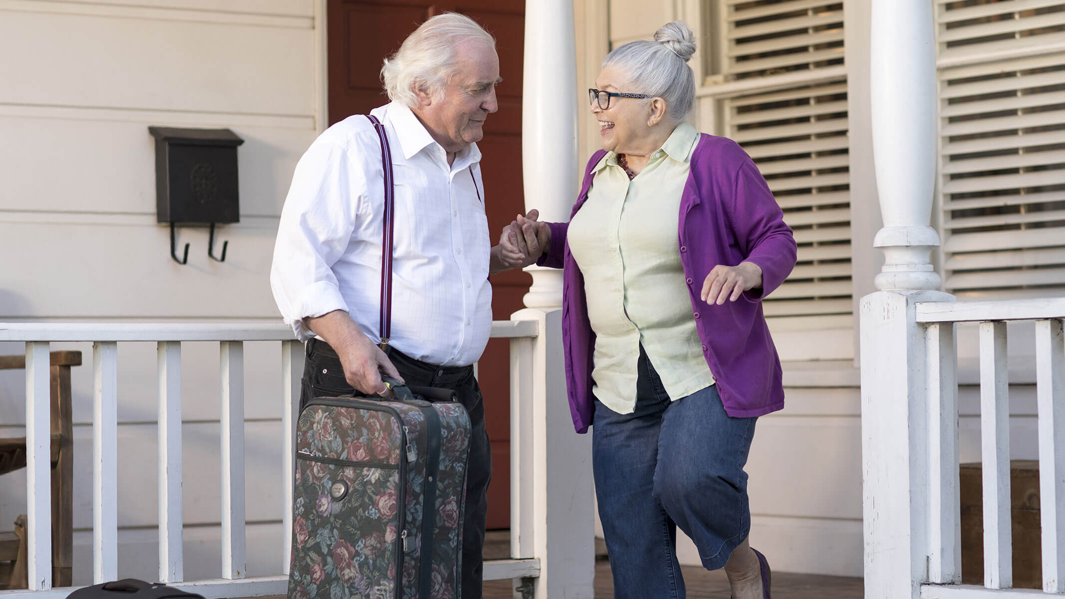An elderly man helps his wife down the front steps while carrying a suitcase.
