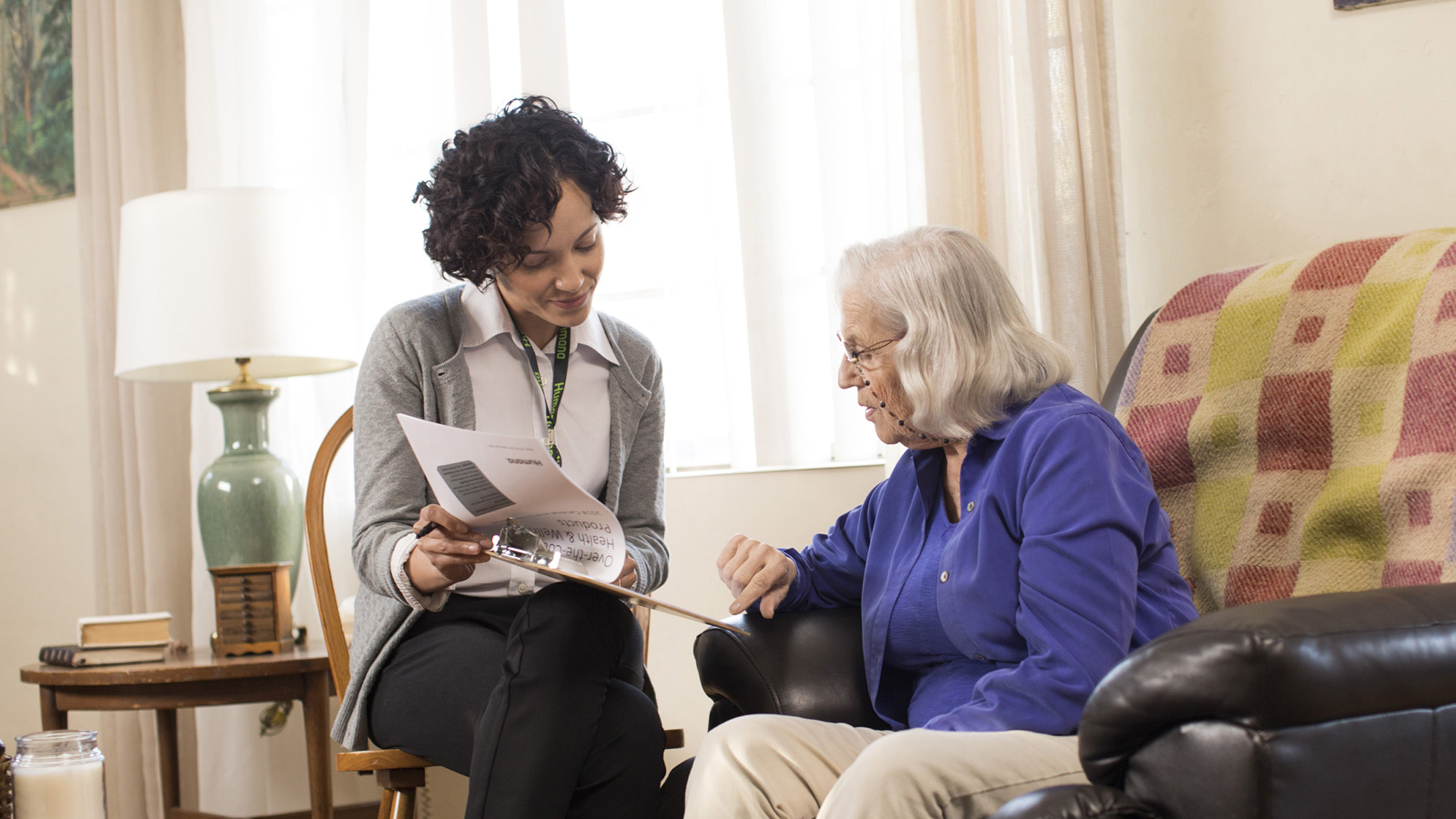 A Humana representative sits down with a senior citizen to complete a set of forms.