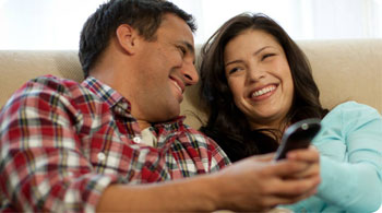 Couple smiling with TV remote