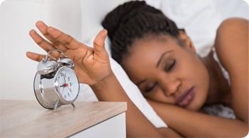 woman laying in bed silencing alarm clock