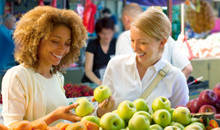 Women buying apples while discussing their prescription options