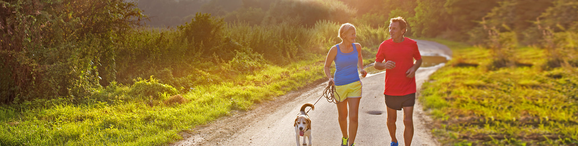 Couple jogging with dog.